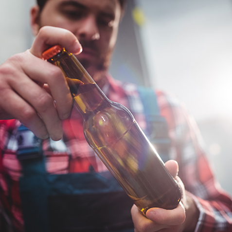 Male manufacturer examining beer bottle at brewery